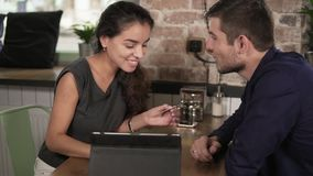 Romantic young couple using tablet and paying with the credit card sitting at the tablet in coffee shop. Happy woman stock video footage
