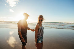 Romantic young couple walking along the sea shore. Outdoor shot of romantic young couple walking along the sea shore holding hands. Young men and women walking Royalty Free Stock Images