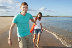 Romantic Young Couple Walking Along Shoreline. Of Beach Holding Hands Royalty Free Stock Photos