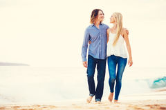 Romantic Young Couple Walking on the Beach Royalty Free Stock Photo