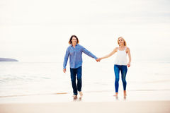 Romantic Young Couple Walking on the Beach Stock Photos