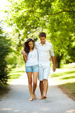 Romantic young couple walking on path in park Stock Photo