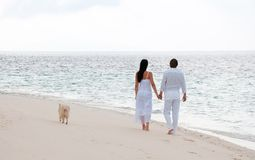 Romantic young couple walking on the sea shore Stock Photo