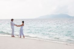 Romantic young couple walking on the sea shore Stock Photography