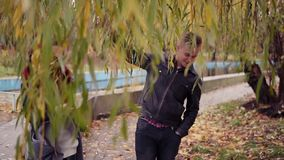 Romantic young couple walking under the tree in autumn park during the day. The blanket of golden leaves on the ground. Warm weather in autumn stock video