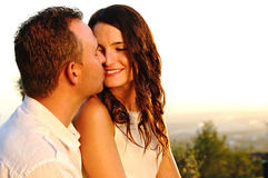 Romantic young couple will kiss at sunset. Romantic young couple dressed in white will kiss at sunset stock photo