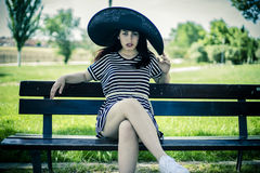 Romantic young girl with big black pigeon sitting on a wooden be Royalty Free Stock Images