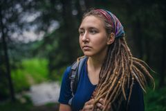 Portrait of a young girl in the forest. Romantic young girl in the forest. Hairstyle dreadlocks. Mysterious nature Royalty Free Stock Image