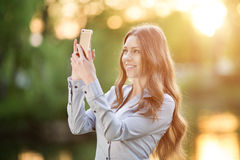Romantic young girl holding a smartphone digital camera with her Royalty Free Stock Photography