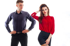 Romantic young girl in a red blouse and with lipstick on lips stands near high guy who looks at her Royalty Free Stock Photography