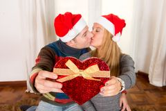 Romantic Young Happy Couple Christmas hats  kissing Royalty Free Stock Images