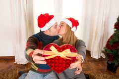 Romantic Young Happy Couple Christmas hats  kissing Stock Images