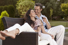Romantic young holding wine glasses on easy chair in park Royalty Free Stock Image