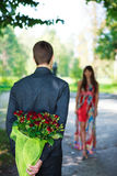 Romantic young man giving a bouquet of red roses to his girlfrie. Nd. Sunny park Royalty Free Stock Photography