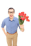 Romantic young man holding a bunch of red tulips Royalty Free Stock Image
