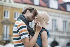 Romantic young man kissing woman against buildings Royalty Free Stock Photo
