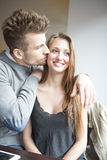 Romantic young man kissing woman in cafe Stock Photography