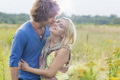 Romantic young man kissing woman in field. Romantic young men kissing women in field Stock Image
