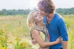 Romantic young man kissing woman in field. Romantic young men kissing women in field Royalty Free Stock Photo