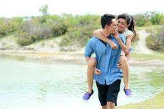 Romantic young man piggybacking his girlfriend Royalty Free Stock Image