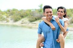 Romantic young man piggybacking his girlfriend Stock Images