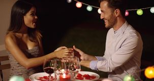 Romantic young man presenting a Valentines gift. To his gorgeous elegant girlfriend as they enjoy a romantic dinner together stock video