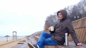Romantic young man relaxing on the beach with , drinking hot tea or coffee from thermos. Calm and cozy evening. 4k stock footage
