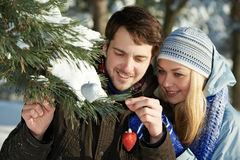 Romantic young peolple in winter. Romantic happy young people with heart decoration in winter outdoors Royalty Free Stock Photo