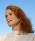 Romantic young woman. With red hair, on the blue sky background Royalty Free Stock Photography