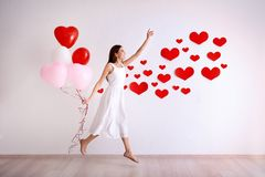 Romantic young woman with balloons near wall. Decorated for Valentine`s Day Royalty Free Stock Photography