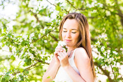 Romantic young woman with closed eyes in the spring garden among apple blossom, soft focus Stock Photography