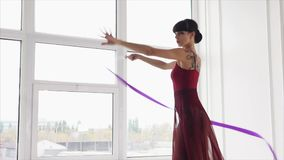 Romantic young woman is dancing with violet ribbon in gymnastic repetition class. Slim and sporty girl is holding and waving ribbon in dance class. She is stock video