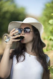 Romantic young woman drinking red wine in vineyard. Royalty Free Stock Photography