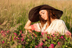 Romantic young woman in hat standing on meadow in hot summer day Stock Photography