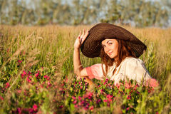 Romantic young woman in hat standing on meadow in hot summer day Royalty Free Stock Photo
