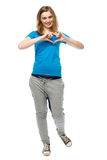 Romantic young woman making a heart gesture Stock Photo