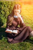 Romantic young woman reading a book in the garden sitting on the grass. Relax outdoor time concept. Stock Image