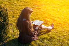 Romantic young woman reading a book in the garden sitting on the grass. Relax outdoor time concept. Royalty Free Stock Photo