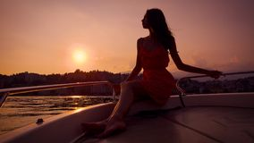 Romantic young woman is sitting on board of small pleasure boat in sunset time, leaning on handrails. Admiring sea view stock video