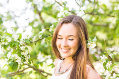 Romantic young woman in the spring garden among apple blossom, soft focus Stock Photo