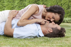 Romantic young woman touching man's lips while lying on him in park Royalty Free Stock Image