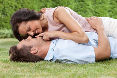 Romantic young woman touching man's lips while lying on him in park Royalty Free Stock Images