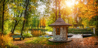 Romantica of the boat station. Little House on the boat station surrounded by autumn trees and the sun through the leaves Royalty Free Stock Images