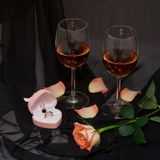 Romantichesy dinner. Wedding ring, wine by the glass, rose Royalty Free Stock Photo