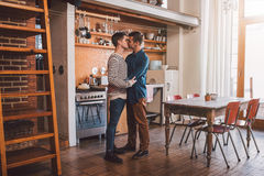 They are romantics at heart. Affectionate young gay couple kissing while standing arm in arm together in their kitchen Stock Photography