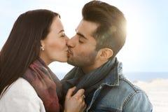 Romantiker kopplar ihop att kyssa på stranden Arkivbilder