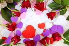 Romantiker noterar: Jag älskar med röda ro och hjärtor Royaltyfria Bilder