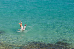 Romantiker nyligen-att gifta sig par som tycker om en sommarsemester Barnet ansar att lyfta hans brud i havet Royaltyfri Bild