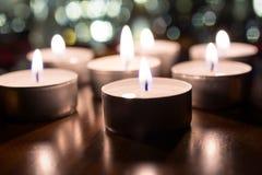 7 romantiker Tealights för matställe på trätabellen med Bokeh på natten Fotografering för Bildbyråer