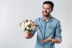 Romantiker uppsökte mannen som ler och rymmer en grupp av blommor Royaltyfri Fotografi
